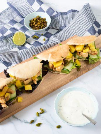 Vier pitabroodjes gevuld met kip, zoetzure komkommer, mango en pistachenootjes. Geserveerd met een frisse saus.