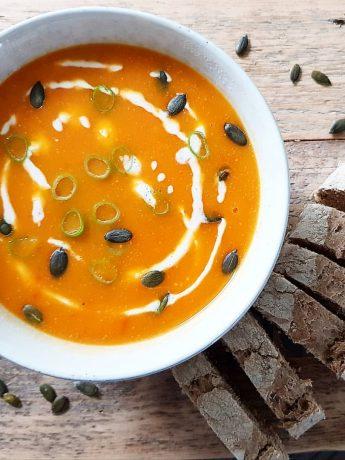 Een kom soep, hgemaakt met pompoen, tomaat, winterpeen, ui, knoflook en kookroom. Lekker met vers brood.