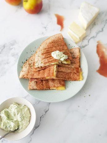 Quesadilla's gevuld met brie, appel en Italiaanse ham. Gebakken in een koekenpan en in vieren gesneden op een bord.