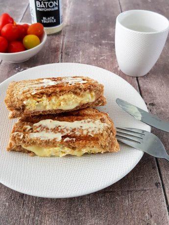 Tosti van twee volkoren boterhammen met roerei, ham en kaas. Geserveerd met truffelmayonaise en snoeptomaatjes.
