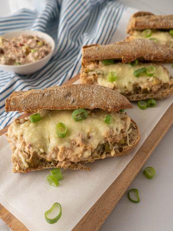 Tuna melt sandwich - Halve baguettes met tonijnsalade, gegratineerd in de oven en in ringen gesneden lente-ui als topping.