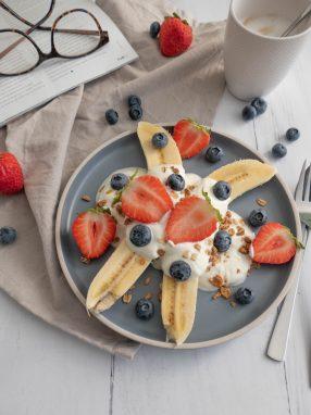 In tweeën gesneden banaan met Griekse yoghurt, blauwe bessen, aardbeien en granola.