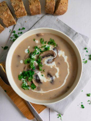 Gebonden champignonsoep met kookroom en fijngehakte peterselie. Geserveerd met vers stokbrood.