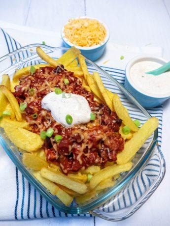 Chili Cheese Fries. Een schaal vol met ovengebakken patat, chili sin carne met bonen en tomatensaus. Gegratineerd met pittige kaas en geserveerd met een frisse witte saus.