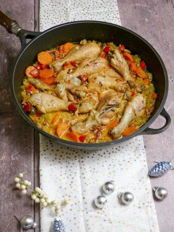 Coq au vin. Drumsticks met diverse groenten als wortel, paprika en bleekselderij, gestoofd in een saus van slagroom en witte wijn met veel groene kruiden.