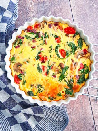 Een in de oven gebakken frittata van ei, spinazie, champignons en tomaat met kruiden en geraspte kaas.