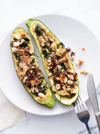 Twee halve courgettes gevuld met spinazie, zongedroogde tomaat feta en gehakte noten. Een heerlijke vegetartische maaltijd uit de oven.