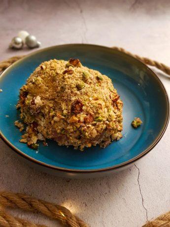 Een in de oven gebakken gevulde rollade met een korstje van gehakte noten. De rollade is gevuld met champignons.