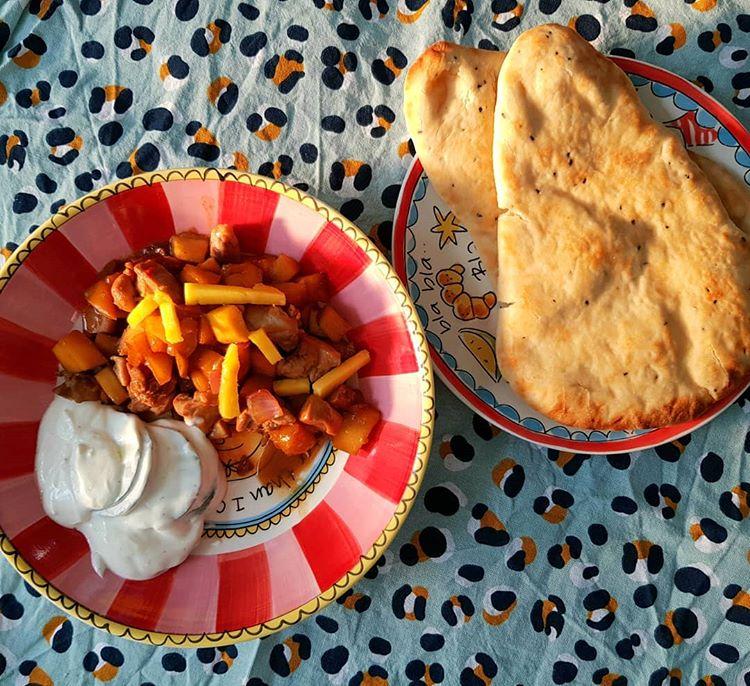 Een kipstoofpotje van kipdijfilet met mango, appel, ui in een licht pittige saus. Geserveerd met naan brood.