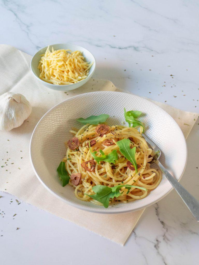 Pasta aglio e olio. Al dente gekookte spaghetti met olijfolie, gebakken plakjes knoflook, kruiden en rucola.