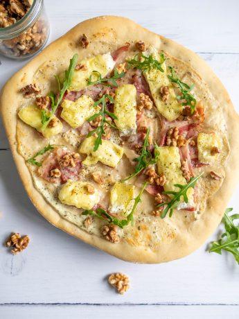 Zelfgemaakte pizzabodem met witte saus, plakjes spek, brie, rucola en gehakte walnoten.