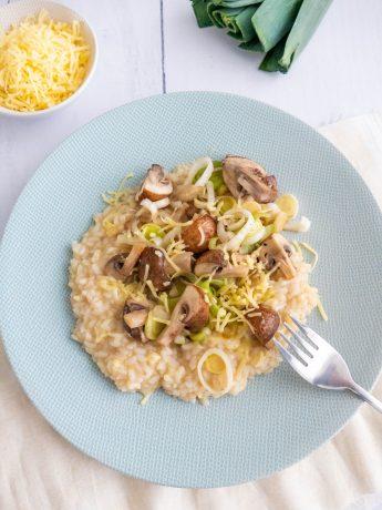 Romige risotto met prei in ringen, champignons in partjes en geraspte oude kaas.