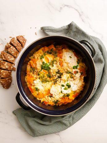 Gepocheerde eieren in tomatensaus met zoete aardappel, tomaat, spinazie, geitenkaas en kruiden. Geserveerd met een in plakken gesneden volkoren baguette.