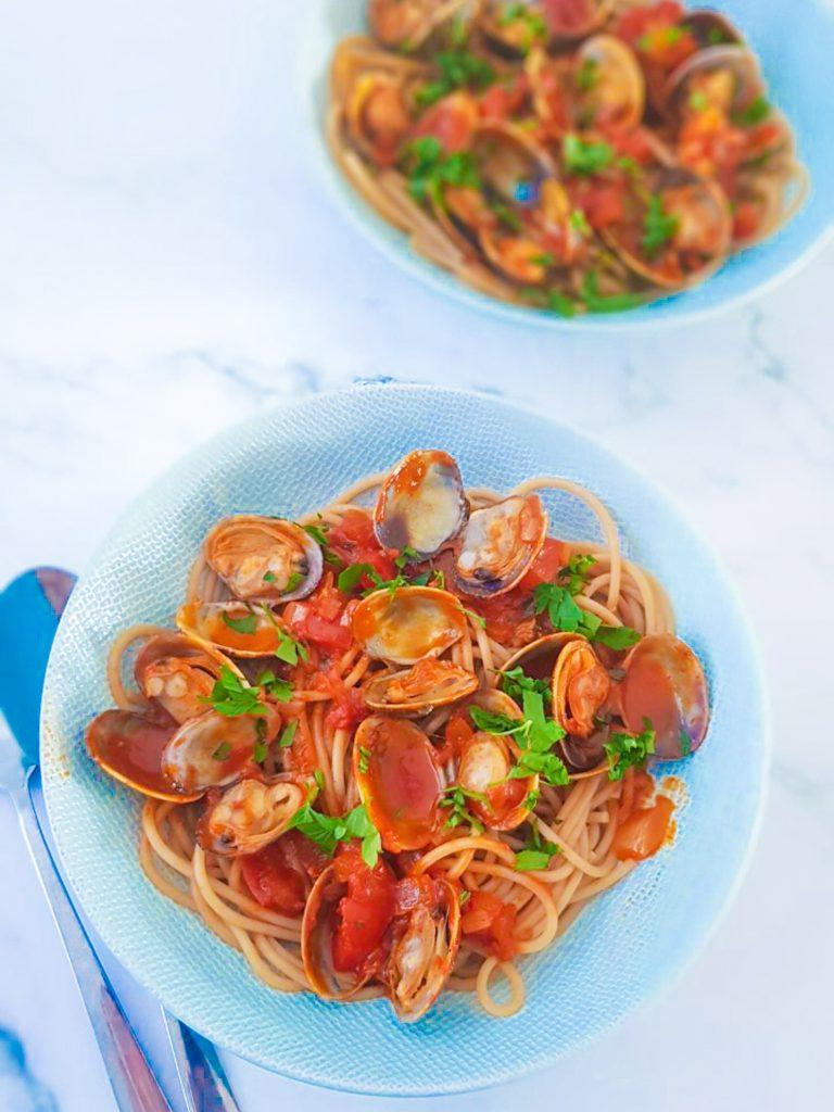 Twee borden met volkoren spaghetti en vongole, venusschelpen, in tomatensaus.