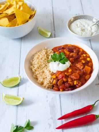 Vegan chili sin carne, met bonen, maïs, vegan gehakt en pittige tomatensaus. Geserveerd met witte rijst, guacamole en tortillachips.