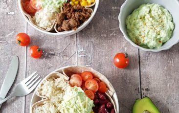 Vegan burrito bowl met rijst, pilled oats, maïs, kidneybonen en cherrytomaten. Geserveerd met guacamole.