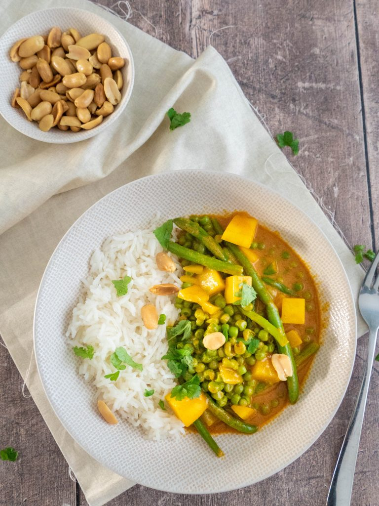 Vegan gele curry met mango, doperwten, pinda's en sperziebonen. Geserveerd met witte rijst.
