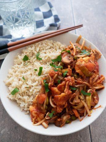 Vegetarische foe yong hai met ei, groenten en een zoet zure tomatensaus. Geserveerd met rijst