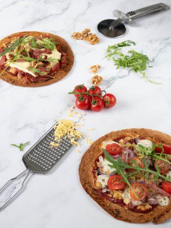 Wrappizza's gemaakt van volkoren wraps. Één belegd met tomatenpuree, mozzarella, ui, tomaat en rucola. De ander belegd met tomatenpuree, spek, brie, walnoten en rucola.