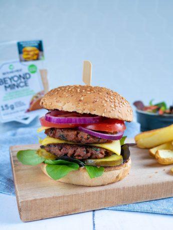 Beyond Mince Smash Burger. Een plantaardige burger met sla, tomaat, ui, augurk en vegan kaas.