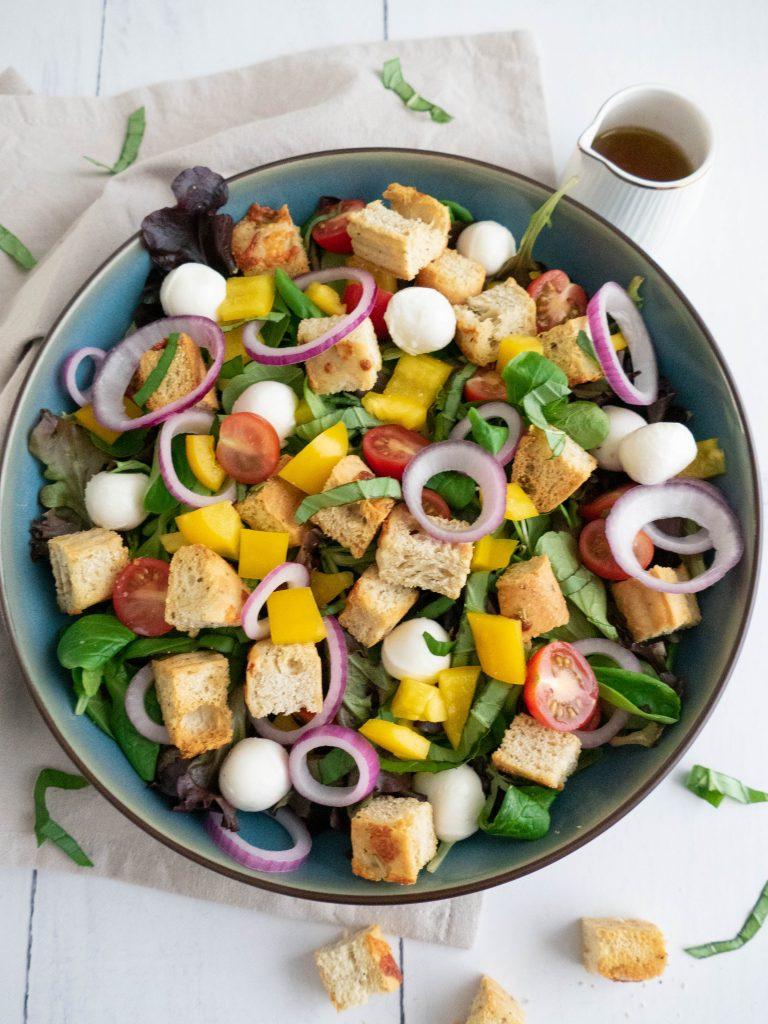 Panzanella, een Italiaanse broodsalade met focaccia, ui, tomaat, mozzarella, paprika en sla. Met een heerlijke dressing.